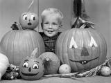 1960s Smiling Blond Boy Surrounded by Pumpkin Patch Jack-O'-Lantern
