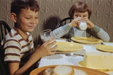 Children Drinking Milk at Dinner Table