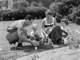 1950s Family in Garden Planting Flowers