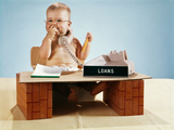 1960s Baby Businessman Diaper Sitting at Loan Desk Wearing Eyeglasses Talking on Telephone