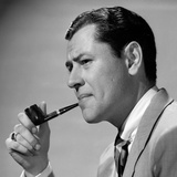 1950s Frowning Businessman in Jacket and Tie Smoking a Pipe