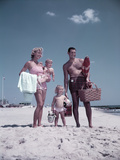 1950s Family Standing at Sandy Beach with Toys and Picnic Basket