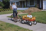 Boy Riding Tricycle and Towing Wagon
