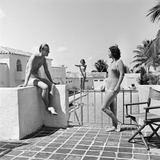 1930s Man Woman Wearing Bathing Suits on Terrace Overlooking Swimming Pool Woman on Diving Board