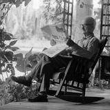 1970s Elderly Man Reading Newspaper on Porch in a Rocker