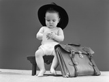 1940s Baby in Fedora Seated on Stool Writing in Notebook with Briefcase at Side