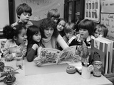 1980s Teacher Reading a Book to Group of School Children