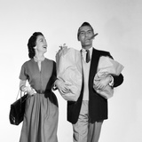 1950s Couple Walking Woman Smiling at Man Carrying Grocery Bags Smoking Cigar