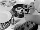 1940s-1950s Woman Hands Frying Eggs in Iron Skillet on Electric Stove Salt and Pepper Shakers