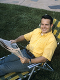 1970s Smiling Man Sitting in Lawn Chair Relaxing Holding Newspaper