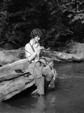 1920s-1930s Woman Sitting on Rock by Side of Stream Wearing Waders Putting Fly on Tippet