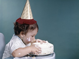 1960s Baby in Highchair Wearing Birthday Hat Eating Whole Birthday Cake