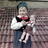 Four Year Old German Boy Stands with His Lederhosen Dressed Doll  Ca 1949