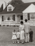 1950s Family of Five with Backs to Camera on Lawn Looking at Fieldstone House