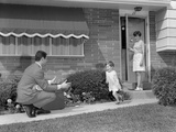 1960s-1970s Little Girl Running to Greet Father on Sidewalk Mother at Front Door