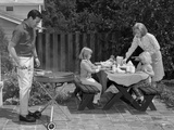 1960s Man Grilling Steak with 2 Daughters Seated at Picnic Table and Wife Standing Serving Food