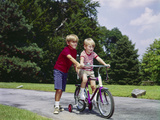 1960s-1970s Boy Helping Little Brother Ride Two Wheel Bicycle with Training Wheels
