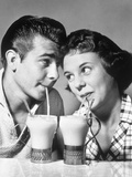 1940s-1950s Romantic Teenage Couple Boy and Girl Head to Head Drinking Ice Cream Sodas