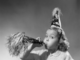 1950s Girl Wearing Party Hat Blowing into Noise Maker