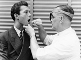 1930s-1940s Doctor Examining Throat of a Young Man