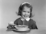 1950s-1960s Smiling Little Girl Eating a Bowl of Breakfast Cereal