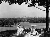 1930s-1940s Family Picnicking under a Tree in Fairmont Park with Skyline of Philadelphia
