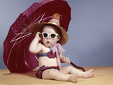 1960s Baby Girl Wearing Two Piece Bikini and Straw Hat Sunglasses Sitting