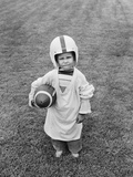 1950s Boy Standing in Grass Wearing Oversized Shirt and Helmet Holding Football