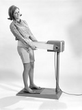 1960s Smiling Young Woman Standing on Weight Reducing Vibrating Exercise Machine