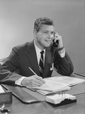 Businessman Seated at Desk Talking on Telephone Smiling Writing with Pencil