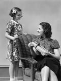 1930s Teenage Girl Daughter Giving a Gift Wrapped Present to Woman Mother Sitting in a Chair
