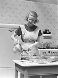 1930s Woman in Kitchen Wearing Apron Making Breakfast Pouring Water into Coffee Pot
