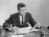 Businessman at Desk Looking over Files Papers Making Notes with Pencil