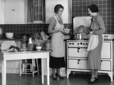 1930s Woman Housewife and Friend Wearing Apron Cooking Food in Kitchen on Gas Stove Indoor
