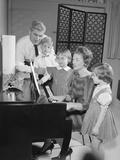 Family Standing around Piano Singing