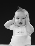 Baby with Hands Up to Side of Head Covering Ears