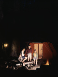1960s Night Scene Family Gazing into Campfire by Tent
