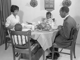 African-American Family at Dining Table with Turkey Saying Grace Praying