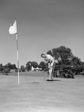 1950s Man Playing Golf Putting Golf Ball on Green to Flag and Cup Outdoor