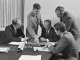 5 Executive Businessmen at Conference Table Meeting Looking over Papers and Blueprints