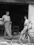 1930s Man Father Holding Hand Tools Talking to Boy Son Leaning in Doorway of Boat Shed