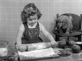 1950s Little Girl Rolling Out Apple Pie Crust on Kitchen Table with Cocker Spaniel Puppy Watching