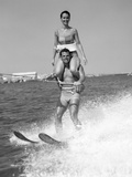 1960s Man Water Skiing with Woman in Bathing Suit Riding on Shoulders