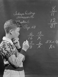 Boy at Blackboard Doing Math Multiplication Problem