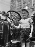 1930s Smiling Boy Standing Next to Fire Engine Wearing Firemans Hat