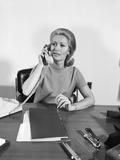 Blond Businesswoman Talking on Telephone Sitting at Desk