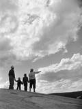 1950s-1960s Family of Four Silhouetted on Top Rocky Hill Pointing at Clouds in Sky