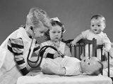 1950s Boy and Girl Playing Doctor and Nurse with Stethoscope and Dolls