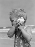 1950s Blond Toddler Girl Listening to Ocean in a Seashell Wearing Teddy Bear Bathing Suit
