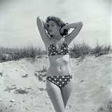 1950s Brunette Bathing Beauty in Polka Dot Bikini Standing in Sand with Hands Behind Head